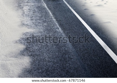asphalt detail of road with snow at winter time - stock photo