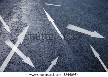 asphalt detail with white chaotic arrows - stock photo