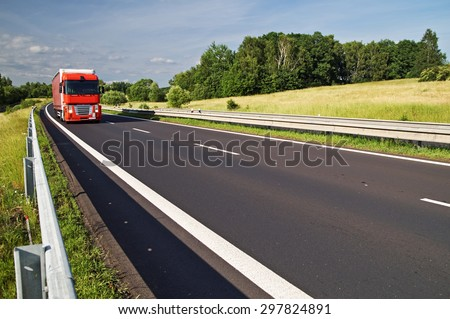 Asphalt expressway with the red truck passing countryside. Sunny day. - stock photo