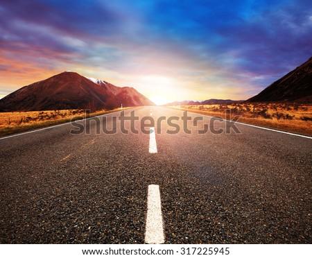 asphalt highway and sun rising mountain landscape - stock photo