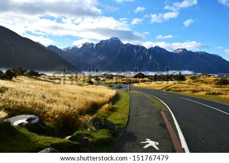 asphalt highway curve road to mountain cook New Zealand with cloud and sky - stock photo