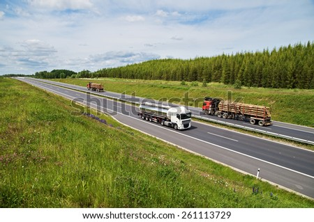 Asphalt highway rising flowering meadows. Tank car and two lorries transporting round timber ride on the road. Larch forest on the horizon. View from above. - stock photo