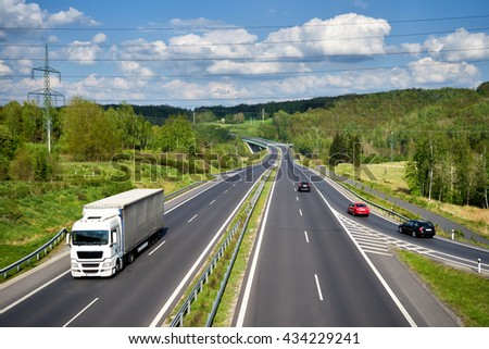 Asphalt highway with a moving white truck between lush forests in the countryside. Passenger cars entering the highway. In the distance the bridge and Electronic toll gate. View from above. - stock photo