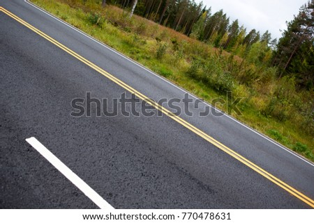 Asphalt highway with yellow lines. Image taken in an angle, yellow line goes from corner to corner.