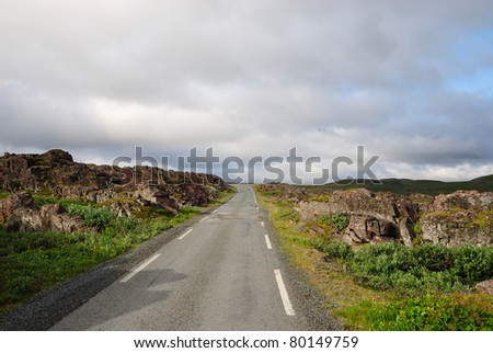 Asphalt narrow road is running among rocks of north Norwegian coast under the overcast sky. This is the road to Hamningberg. Highway is photographed with diminishing perspective. - stock photo