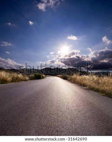 asphalt of country road in backlit - stock photo