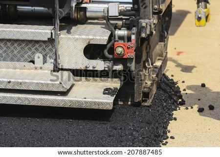 asphalt paver machine during road construction and repairing works  - stock photo