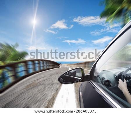 Asphalt road along a blue tropical sea - stock photo