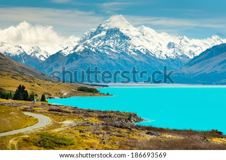 asphalt road along Lake Pukaki view from Glentanner Park Centre near Mount Cook; on a background of blue sky with clouds; snowy Southern Alps. - stock photo