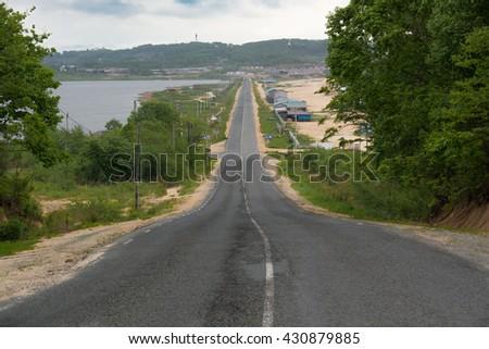 Asphalt Road Along The Pond. Asphalt Road Along The Reservoir. Receding into the distance. - stock photo