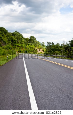 Asphalt road along with tropical forest zigzag ahead. - stock photo