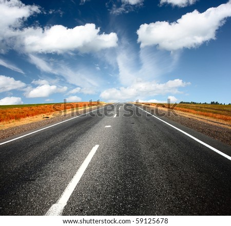 Asphalt road and blue sky with clouds - stock photo