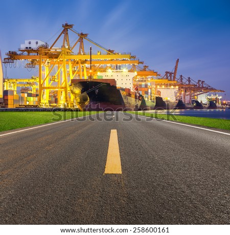 Asphalt road and cargo freight ship and cargo container working with crane at port, twilight time. - stock photo