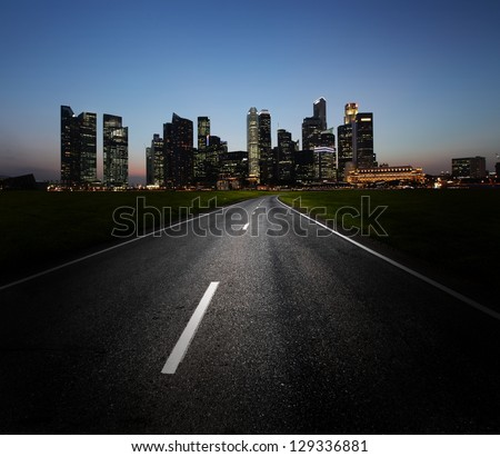 Asphalt road and city with illuminated buildings on the horizon - stock photo