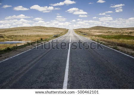 asphalt road and clouds on blue sky in summer day