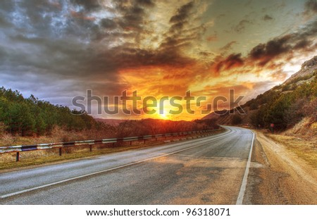 Asphalt road and evening sun in clouds - stock photo