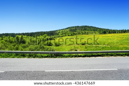 asphalt road and green hill with trees, summer landscape in mountains - stock photo