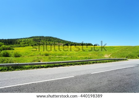 asphalt road and green trees on hill, summer landscape in mountains - stock photo