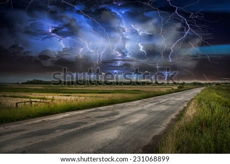 Asphalt road and lightning storm - stock photo