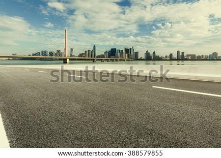 Asphalt road and modern city skyline - stock photo