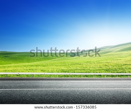 asphalt road and perfect green field - stock photo