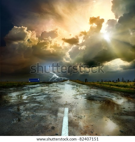 Asphalt road and the puddles at sunset - stock photo