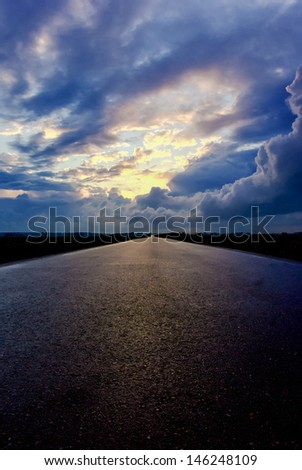 Asphalt road and the sky with dark clouds - stock photo