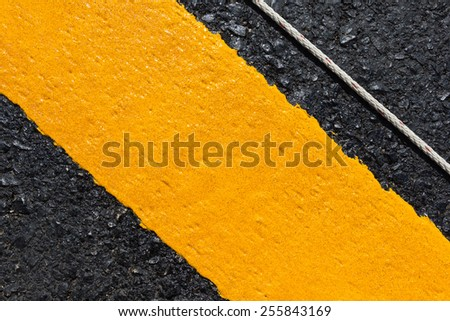 Asphalt road as abstract background, yellow line on the road texture.