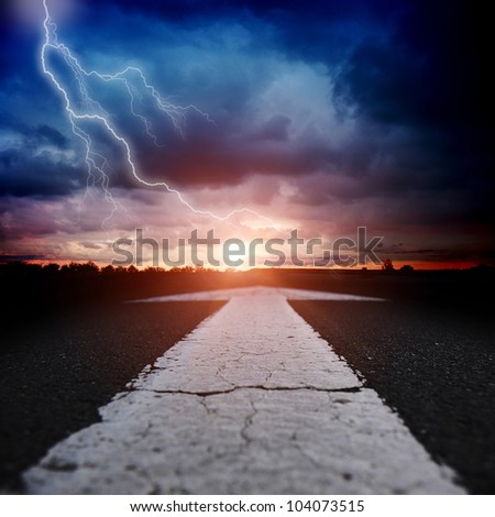 asphalt road at dusk with an arrow - stock photo
