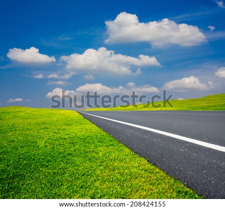 asphalt road beside hill of green meadow with blue sky in bright day