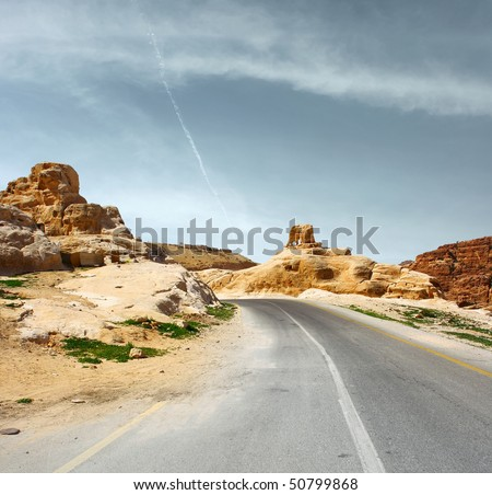 Asphalt road blue sky with clouds and mountains - stock photo