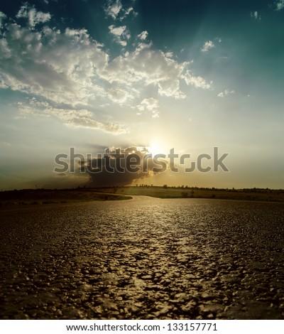 asphalt road close up to dramatic sunset - stock photo