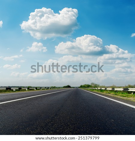 asphalt road closeup and low clouds in blue sky - stock photo