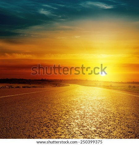 asphalt road closeup and sunset over it - stock photo