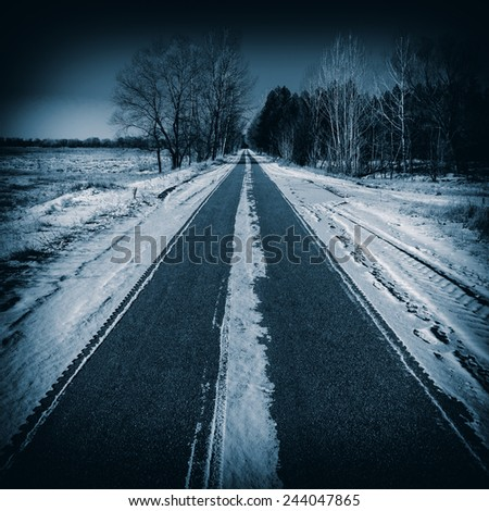 asphalt road covered with snow in the countryside, winter season