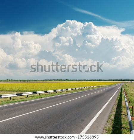 asphalt road goes to cloudy horizon - stock photo