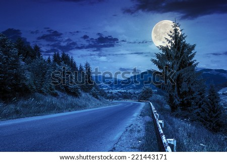 asphalt road going off into the distance on the left, passes through the green shaded forest at night in full moon light - stock photo