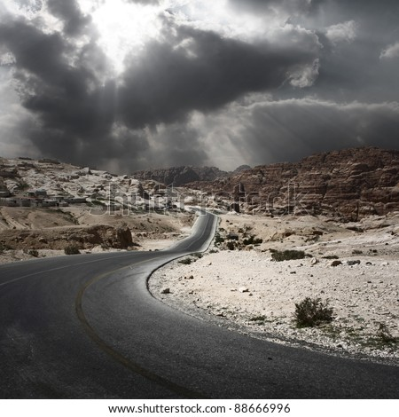 Asphalt road in a desert with dark cloudy sky on the background - stock photo