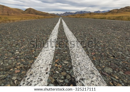 Asphalt road in a mountainous area on the border between Russia and Mongolia - stock photo