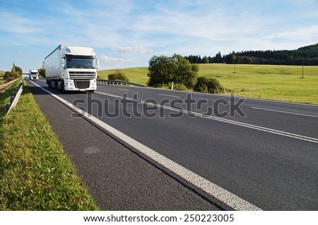 Asphalt road in a rural landscape. The arriving two white trucks on the road. Meadow and forest in the background. - stock photo