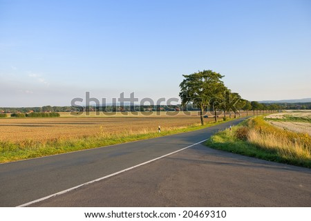 Asphalt road in a rural summer landscape - stock photo