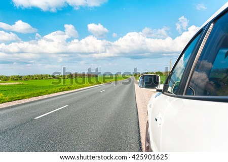 Asphalt Road in fields with white car standing on wayside. Colorful summertime outdoors horizontal image with perspective.