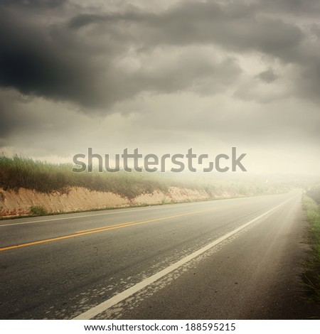 Asphalt road in forrest and rainclouds - stock photo