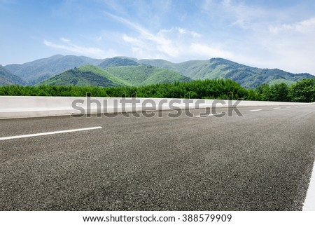 asphalt road in front of the green mountain
