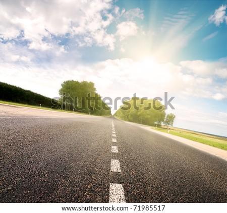 Asphalt road in green meadow. Belarus. Golden sunset. - stock photo