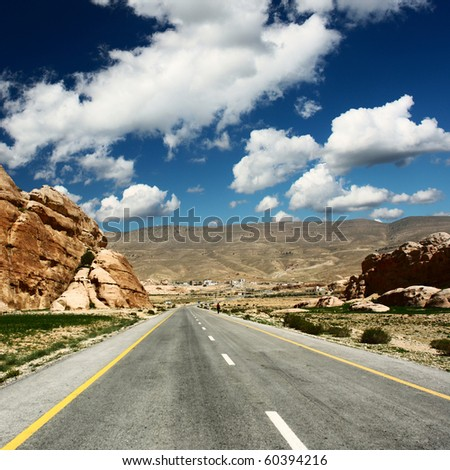 Asphalt road in mountains - stock photo