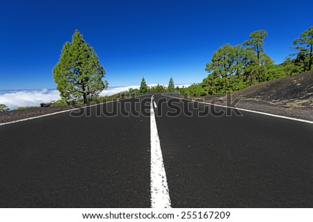 Asphalt road in mountains above clouds - stock photo
