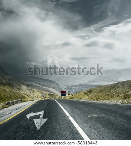 Asphalt road in mountains with arrows and storm dark clouds over valley - stock photo