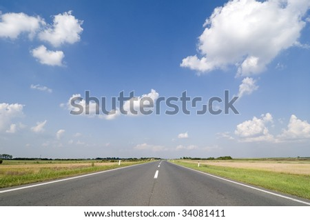 Asphalt road in perspective with blue sky and white clouds