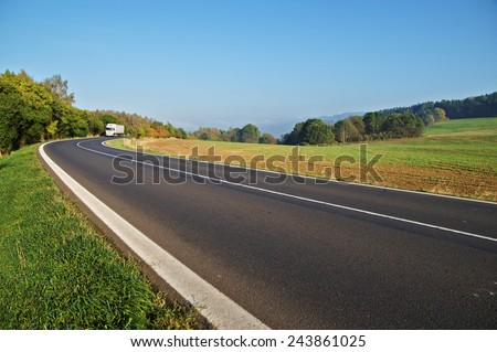 Asphalt road in the countryside, white truck coming around in the distance the bend, forest on the horizon - stock photo
